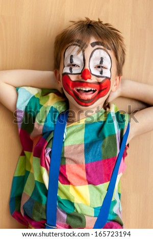 Smiling little boy masked as a clown