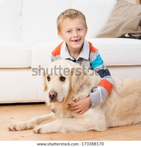 Smiling little boy missing his front teeth bending down playing with a golden retriever on the living room floor and grinning at the camera