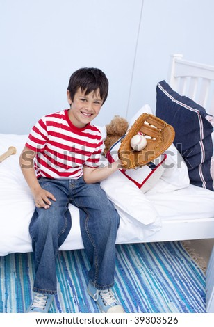 Smiling little boy playing baseball in his bedroom - stock photo