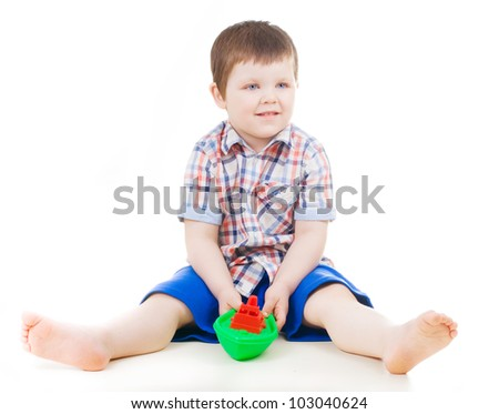Smiling little boy  playing with toy boat - stock photo