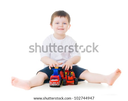 Smiling little boy playing with toy cars