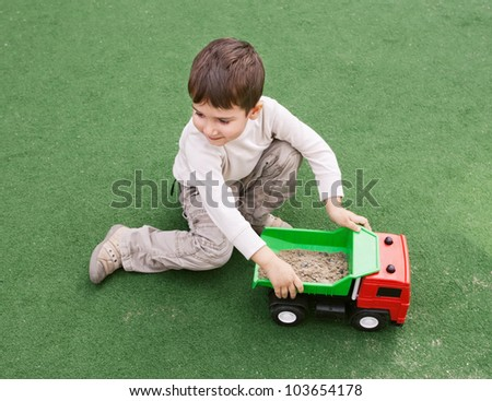 Smiling little boy plays on green grass with toy car - stock photo