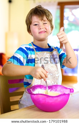 Smiling little boy preparing cake at home cooking