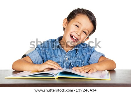 Smiling little boy reading a book. - stock photo
