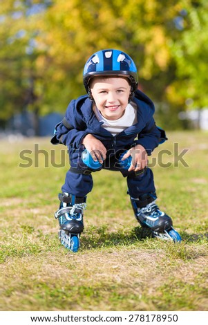 Smiling little boy riding on roller skates in the park - stock photo