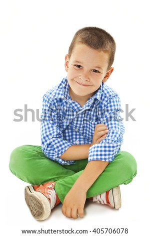 Smiling little boy sitting down on floor and looking at camera. Isolated on white background  - stock photo