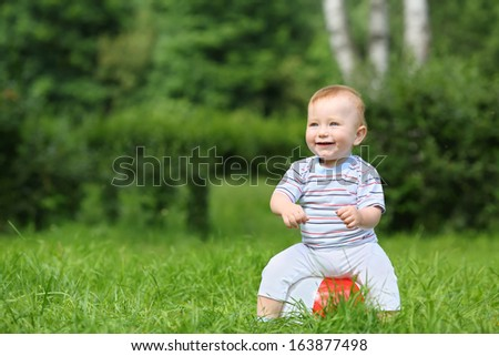 Smiling little boy sitting on an inflatable ball in the park