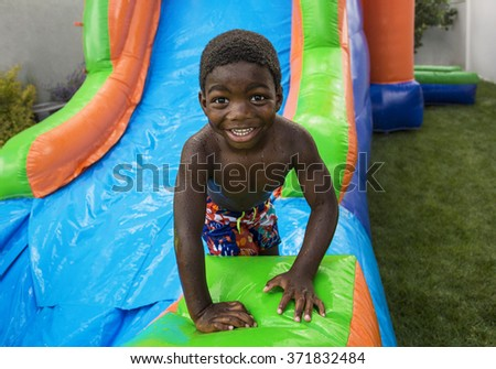 Smiling little boy sliding down an inflatable bounce house - stock photo