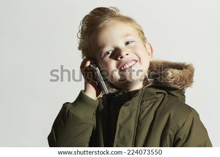 smiling little boy talking on the cellphone. happy child in winter coat. fashion kids.children - stock photo