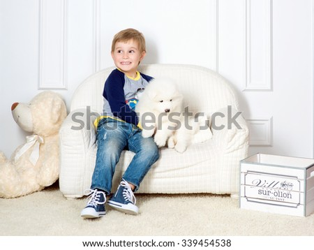 smiling little boy three years old playing with white puppy of Samoyed in studio