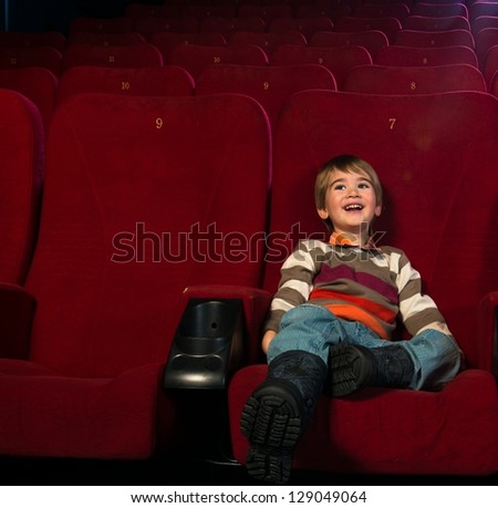 Smiling little boy watching movie in a cinema - stock photo