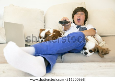 Smiling little boy watching TV - stock photo