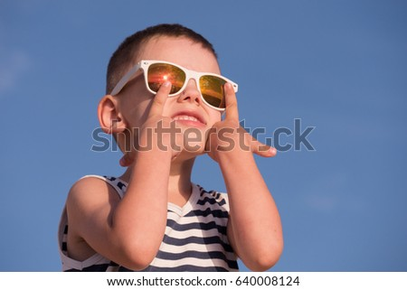 smiling little boy wearing sunglasses with sea sunset reflection and striped shirt touching his sunglasses with fingers on blue sky background