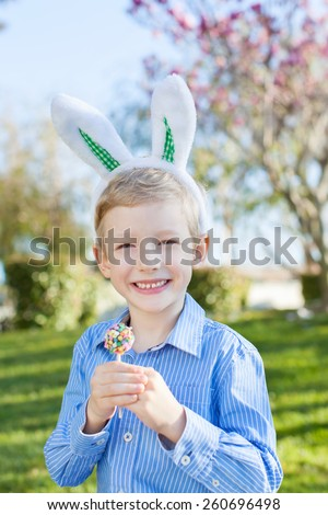 smiling little boy with easter bunny ears holding colorful candy after egg hunt at spring time - stock photo