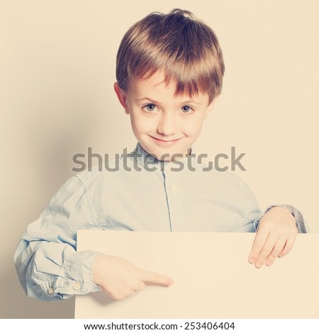 Smiling little boy with empty paper blank in hands - stock photo
