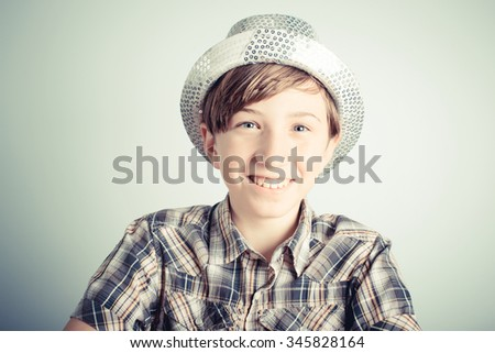 smiling little boy with party hat on gray background - stock photo