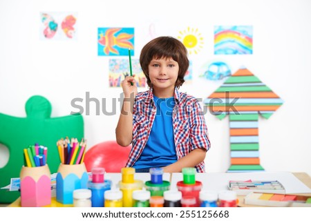 Smiling little boy with pencil in hand looking at camera. Boy studying in preschool center for children. Table is full of cans with paints and colored pencils - stock photo