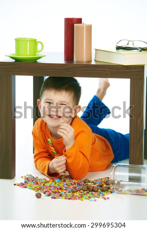 Smiling little boy with sweets under table at home indoor. Laying on belly, looking at camera, isolated on white. - stock photo