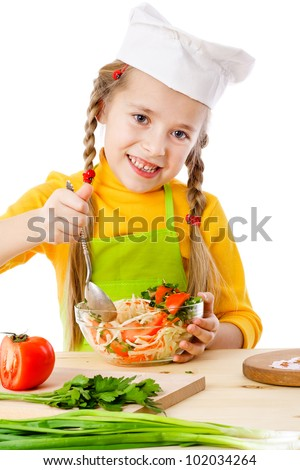 Smiling little chef mix the salad, isolated on white - stock photo