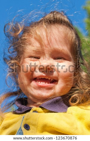 Smiling little child against the sky in the sunlight close-up view from below.