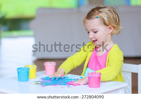 Smiling little child, blonde artistic toddler girl painting with colorful finger paints indoors at bright room at home or kindergarten  - stock photo