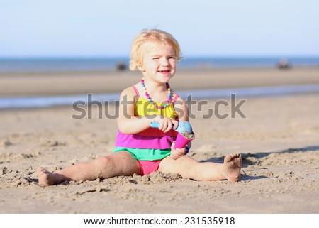 Smiling little child, blonde toddler girl wearing colorful necklace and swimsuit playing with plastic ice cream cone toy sitting in dunes on sandy beach at North Sea - stock photo