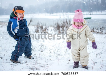 Smiling little children playing together on snowy day in winter park.