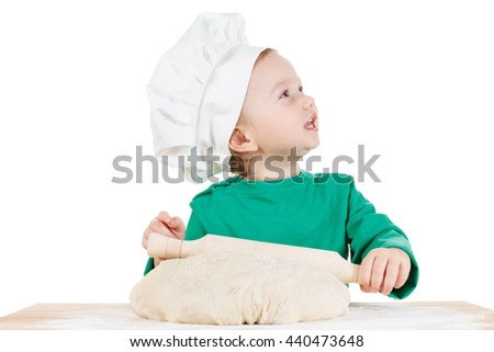 Smiling little cook boy kneading the dough for the cookies, isolated on white background.  Half-length portrait of the table in studio - stock photo