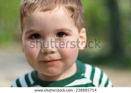 Smiling little cute boy looks at camera in park. Shallow dof - stock photo