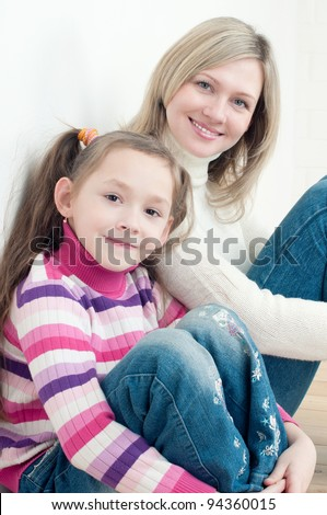Smiling little girl and her mom sitting on the floor at home and looking at camera