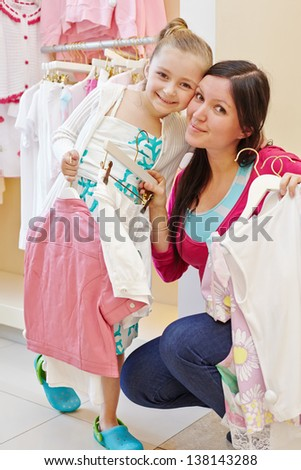 Smiling little girl and her mother cheek to cheek in clothing store, hangers with clothes in their hands - stock photo