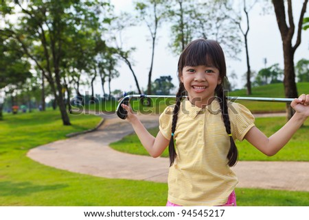 Smiling little girl at golf course - stock photo