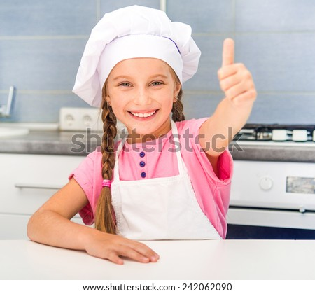 smiling little girl at home in the kitchen - stock photo