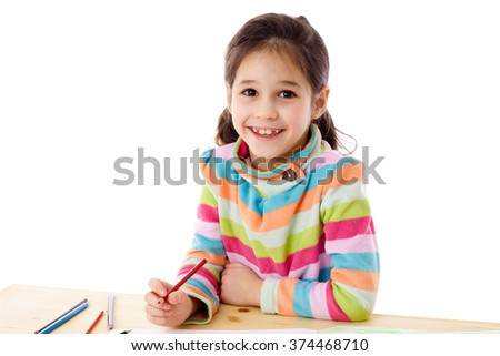 Smiling little girl at the table draw with crayons, isolated on white - stock photo