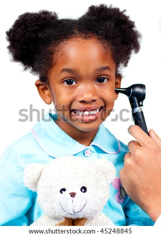Smiling little girl attending medical check-up holding a teddy bear isolated on a white background - stock photo