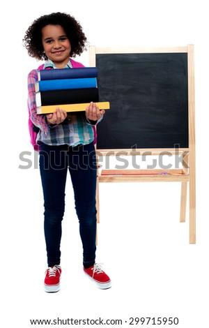 Smiling little girl carrying school books over white - stock photo