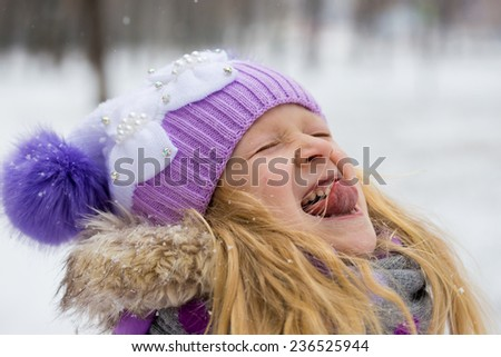 smiling little girl catching a snowflakes with her tongue  - stock photo