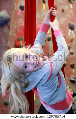 Smiling little girl climbing on rope - stock photo