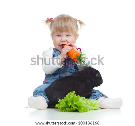 Smiling little girl eating a carrot and feeding rabbit with lettuce on the floor