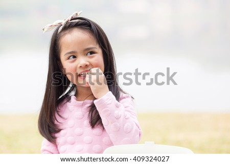 smiling little girl eating cookie