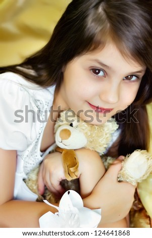 Smiling little girl embraces teddy bear and looking in a camera