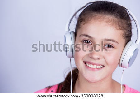 Smiling Little girl enjoying music in headphones at home relaxing. Relaxed little girl listening to music with earphones  looking serene and happy. - stock photo