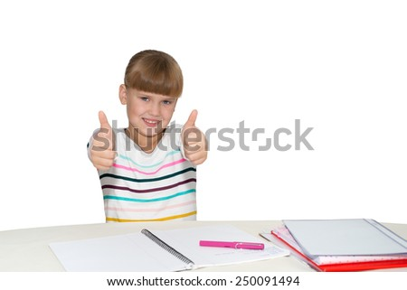 Smiling little  girl gesturing thumbs up at desk isolated - stock photo