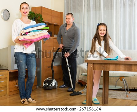 Smiling little girl helping happy parents to clean at home. Focus on woman - stock photo