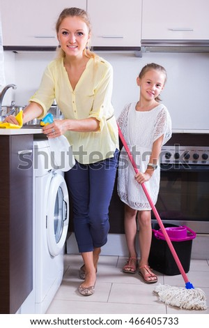 Smiling little girl helping happy young woman  doing regular cleanup at kitchen