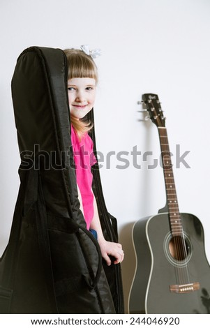 Smiling little girl hiding in a guitar's cover, white background - stock photo