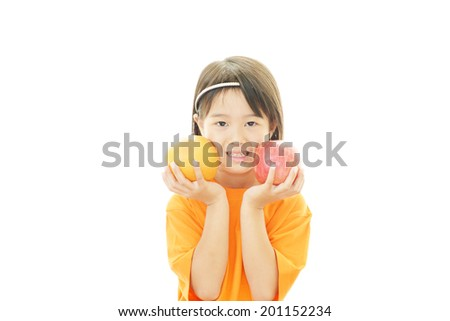 Smiling little girl holding fruits - stock photo