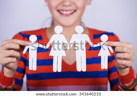 Smiling little girl holding paper cut of family.Family Life Insurance.Protecting family, family concepts.