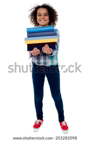 Smiling little girl holding stack of school books - stock photo