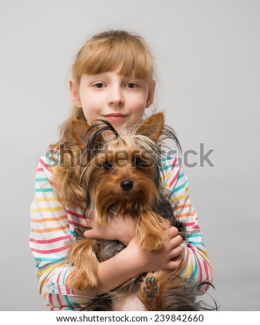 smiling little girl hugging a yorkshire terrier dog in an outdoor setting